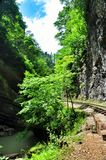 Railway in Guam gorge on one side of the rocks, the other a deep precipice and seething fast river. Railway in Guam gorge on the edge of precipice for the Royalty Free Stock Photo