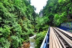 Railway in Guam gorge on one side of the rocks, the other a deep precipice and seething fast river Stock Photos