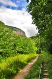 Railway in Guam gorge on one side of the rocks, the other a deep precipice and seething fast river. Railway in Guam gorge on the edge of precipice for the Royalty Free Stock Images