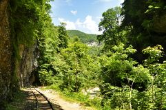 Railway in Guam gorge on one side of the rocks, the other a deep precipice and seething fast river Stock Image