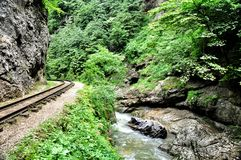 Railway in Guam gorge on one side of the rocks, the other a deep precipice and seething fast river. Train wreck, which at the turn of the railway in Guam gorge Royalty Free Stock Images
