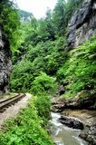 Railway in Guam gorge on one side of the rocks, the other a deep precipice and seething fast river Stock Photography