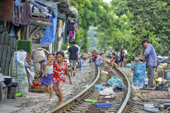 Railway in Hanoi, Vietnam. People are living on and next to the railway in Hanoi. When the train comes they have to move there things and get out of the way Stock Images