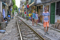 Railway in Hanoi, Vietnam. Tourists walking across the railway in Hanoi. When the train comes people  who are living at the railway have to move there things and Royalty Free Stock Image