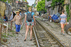 Railway in Hanoi, Vietnam. Tourists walking across the railway in Hanoi. When the train comes people  who are living at the railway have to move there things and Stock Photos