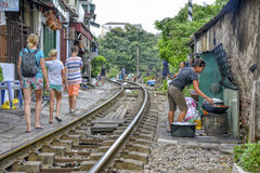 Railway in Hanoi, Vietnam. Tourists walking across the railway in Hanoi. When the train comes people  who are living at the railway have to move there things and Stock Images