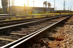 Railway and industrial buildings on a bright sunny day, diminishing perspective. Railway, rails, sleepers and industrial buildings on a bright sunny day royalty free stock photos