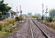 Railway intersection with the automatic barrier. Railway intersection with the automatic barrier in the local road,countryside of Thailand Royalty Free Stock Image