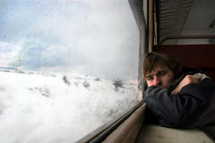 Railway journey. Young man traveling by train through the winter landscape Royalty Free Stock Photos