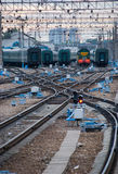 Railway junction. Perspective of crossing rails, traffic lights and train Stock Photo