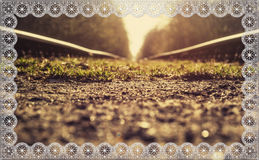 Railway lace frame. Background basis beautiful sunset, railroad, fine grass, lace frame, beautiful vintage, floral cobweb. Using the design for registration of Royalty Free Stock Photo