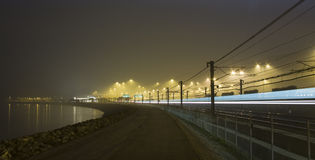 Railway and lake. Rails by night with reflecting neon light Royalty Free Stock Image