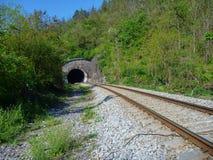 Railway leading to the dark tunnel entrance Stock Photos