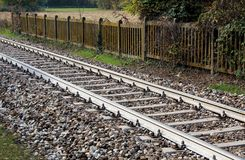 Railway line bordered by a concrete fence. In the countryside Royalty Free Stock Photography