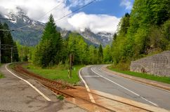 Railway line crossing the road. The road crosses the railway line with mountains in the background royalty free stock photos