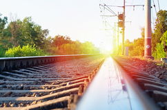 Railway line and a traffic light. Against the backdrop of sunset Royalty Free Stock Image