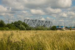 Railway metal bridge and summer meadow with high grass. Railway gray metal bridge and beautiful summer meadow with high grass and flowers royalty free stock photography