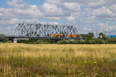 Railway metal bridge and summer meadow with high grass. Railway gray metal bridge and beautiful summer meadow with high grass and flowers royalty free stock image