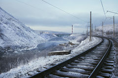 Railway near the river, mountain in winter. Railway near the river, mountain and city in winter Royalty Free Stock Photography