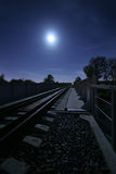Railway at night. Long railway in the light of the full moon Royalty Free Stock Image