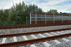 Railway with noise damping wall. Stock Photos