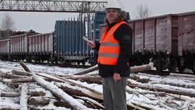 Railway officer using tablet PC near to freight wagons. In winter   day stock video