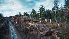 Railway path between red granite stones and rocks Royalty Free Stock Images
