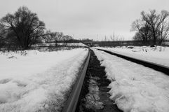 Railway. The picture monochrome. It`s spring. Photo showing the path of the railway somewhere in Russia. Immense space. Lonely freight car in the distance on stock photo