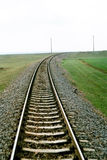 Railway on plain field. Landscape with railway curving to the right Royalty Free Stock Photography