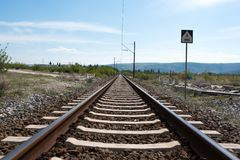 Railway rails with electric poles and in the background of the mountain. The picture shows the newly built railway infrastructure incorporated into the natural royalty free stock image