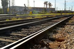 Railway, rails, sleepers and industrial buildings on a bright sunny day. Diminishing perspective royalty free stock image