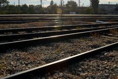 Railway, rails, sleepers and industrial buildings on a bright sunny day. Diminishing perspective stock photography