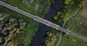 Railway through river. Railway bridge above the river. Bird eye view on a railway bridge which going above the river. Beautiful autumn nature. Reflection in stock footage