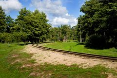 Railway road in nature park. Small railway track in beautiful nature park on a summer day in city of Ventspils, Latvia. This is a clean and green park near the Royalty Free Stock Photography