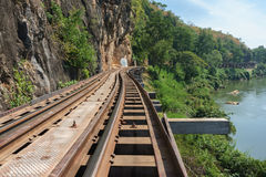 Railway between rocky cliff and river in Kanchanaburi, Thailand stock images
