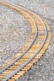 Railway on rocky ground viewed on a sunny day. CLose up of a railway track viewed on a bright and sunny day. The railroad track curves through the rough rocky royalty free stock photo