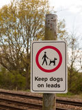 A Railway Safety Sign Saying Keep Dogs on Leads in White and Red