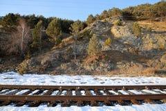 Railway on the shore of lake Baikal. Rails and sleepers on the old railway land krugobajkalsky below the steep coastal cliffs of lake Baikal Stock Photos