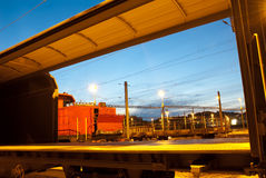 Railway shot trough a freight train car at twiligh Royalty Free Stock Images