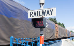 Railway sign and passing cargo train Stock Images