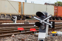 Railway signaling and a passing train. Signaling device at the railroad tracks and the train with containers royalty free stock image