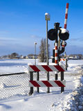 Railway signs and barrier. At a railway crossing in the country with snow Stock Photo