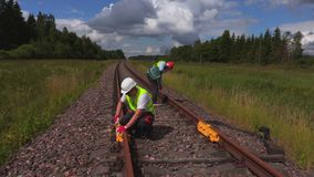 Railway staff checks switches on railway track. In summer day stock video footage