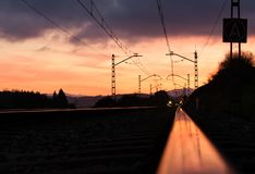 Railway station against beautiful sky at sunset. Industrial landscape with railroad, colorful blue sky with red clouds, sun royalty free stock images