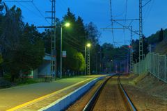 Platform of railway station and railroad at twilight Royalty Free Stock Photos
