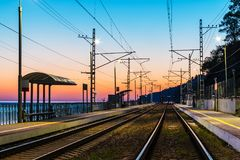 Platform of railway station and railroad at twilight Royalty Free Stock Image
