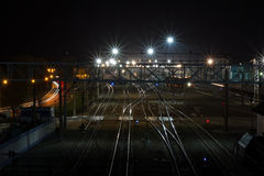 Railway station at night. Brilliant rails and concrete sleepers at night. Rails run away into the distance, toward the lights of the big city Stock Photo