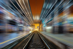 Railway station at night with motion blur effect. Railroad Royalty Free Stock Photo