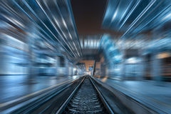 Railway station at night with motion blur effect. Railroad Royalty Free Stock Photography