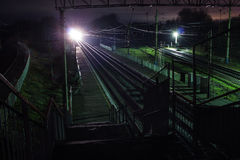Railway station at night with a passing train Stock Photography